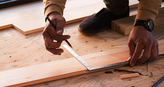 定規で木材を図る男性の手